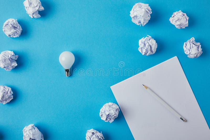 Top view of power saving light bulb with crumpled papers. On blue surface royalty free stock photography