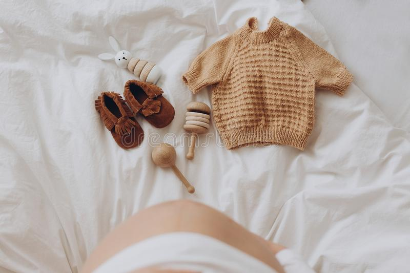 Top view of pregnant woman belly bump and stylish brown boho shoes, clothes and wooden toys for baby on white bed at home. Stylish. Pregnant mom waiting for royalty free stock images