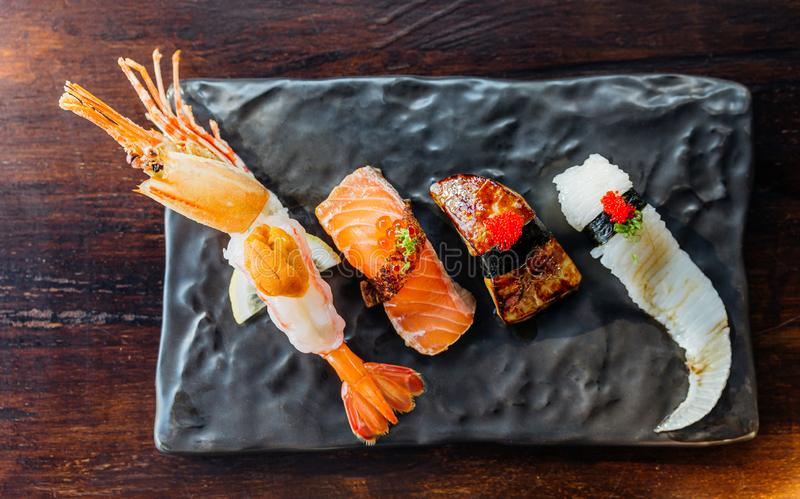 Top view of Premium Sushi Set include Deep fried Shrimp with Sea Urchin, Foie Gras, Salmon and Engawa on The Black Stone Plate royalty free stock photo