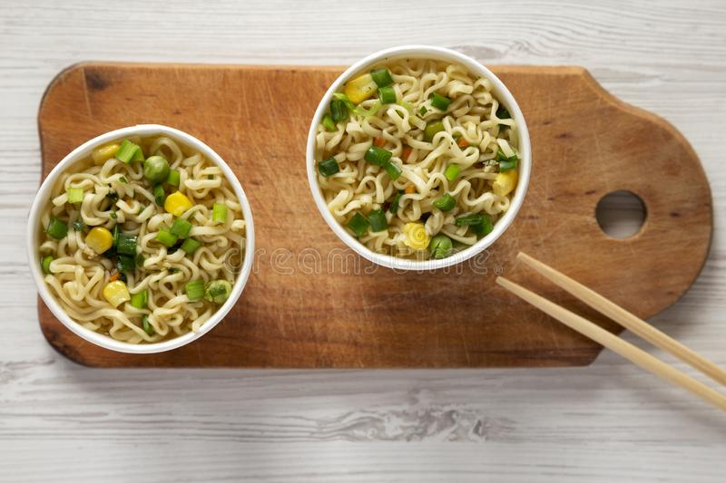 Top view, prepared instant noodles with beef flavoring in cups over white wooden background. Flat lay, from above, overhead royalty free stock image