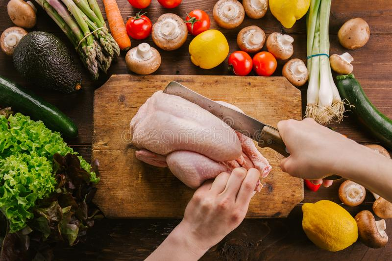 Preparing cooking process with poultry and season vegetables. Top View of Preparing Cutting fresh raw chicken. Hands of young cook cut poultry on an old vintage royalty free stock photography