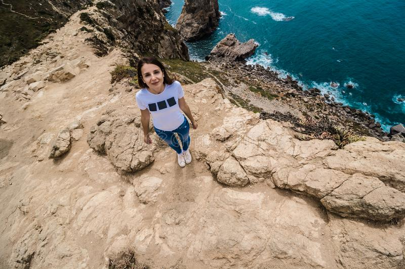top view of pretty woman in a white t-shirt and blue jeans standing on the rocky edge of the cliff. The waves of the ocean break stock images