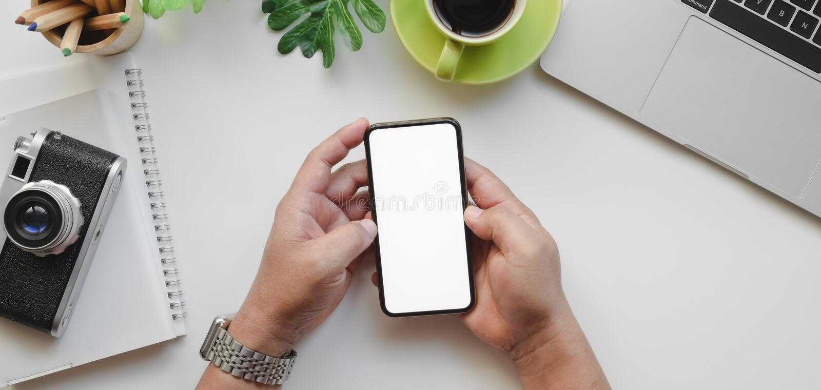Top view of professional male designer holding blank screen smartphone in his workplace. With camera and office supplies stock image