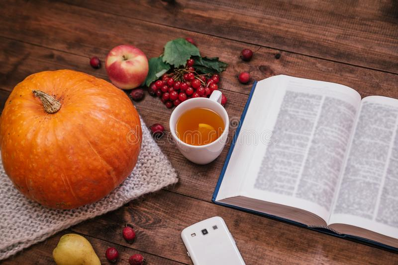 Top view of a pumpkin, apples and a book, phone on wooden table royalty free stock photography