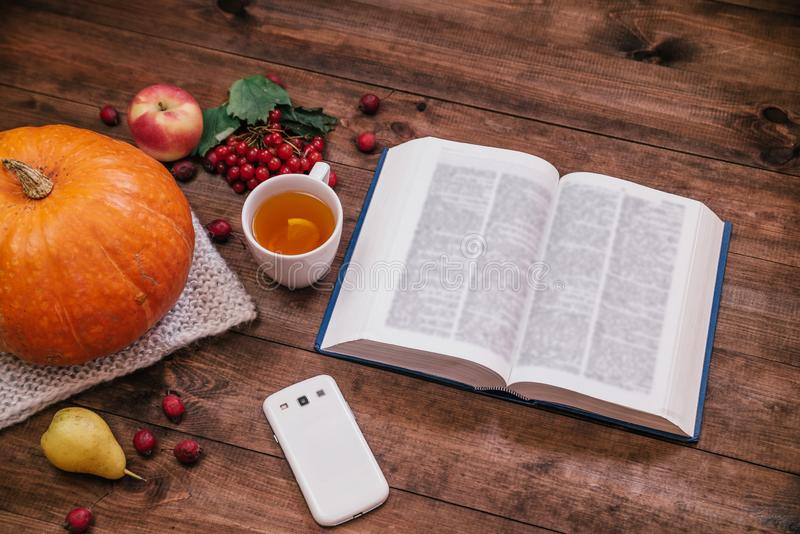 Top view of a pumpkin, apples and a book, phone on wooden table royalty free stock photos