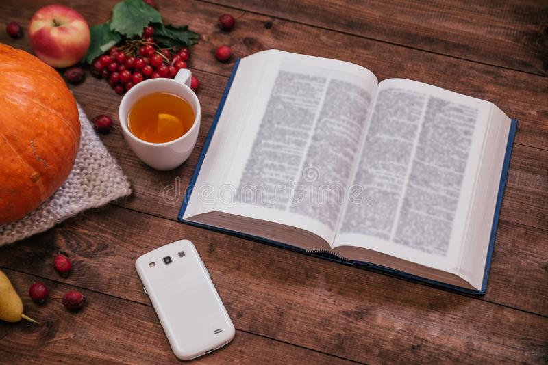 Top view of a pumpkin, apples and a book, phone on wooden table royalty free stock image