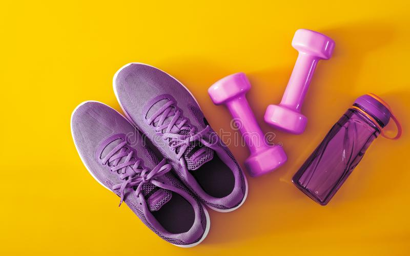 Top view of purple and violet sport shoes, dumbbells and bottle of water on yellow background. Fitness and Healthy lifestyle. Background concept accessories royalty free stock images