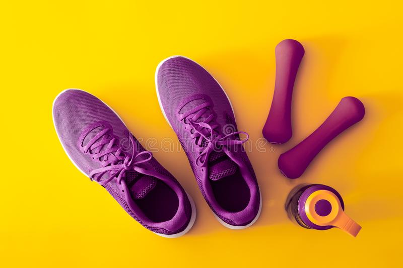 Top view of purple and violet sport shoes, dumbbells and bottle of water on yellow background. Fitness and Healthy lifestyle royalty free stock photography