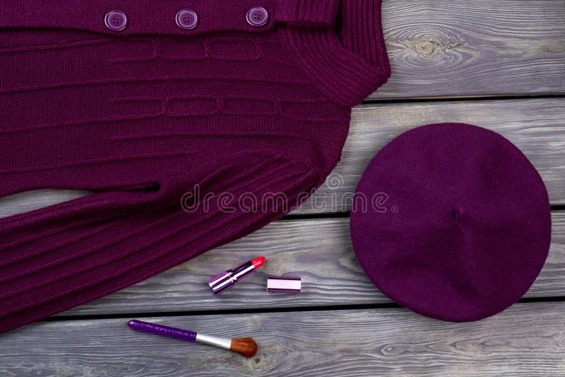 Top view purple winter clothes and cosmetic for make up. Wooden desk surface background royalty free stock photo