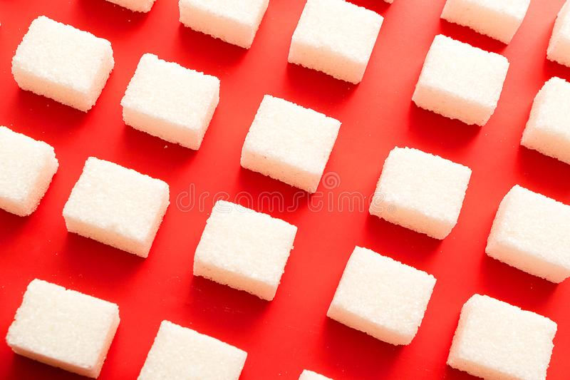 Top view of the sugar lying on a red background. Lots of pieces of sugar lined up in rows stock photography