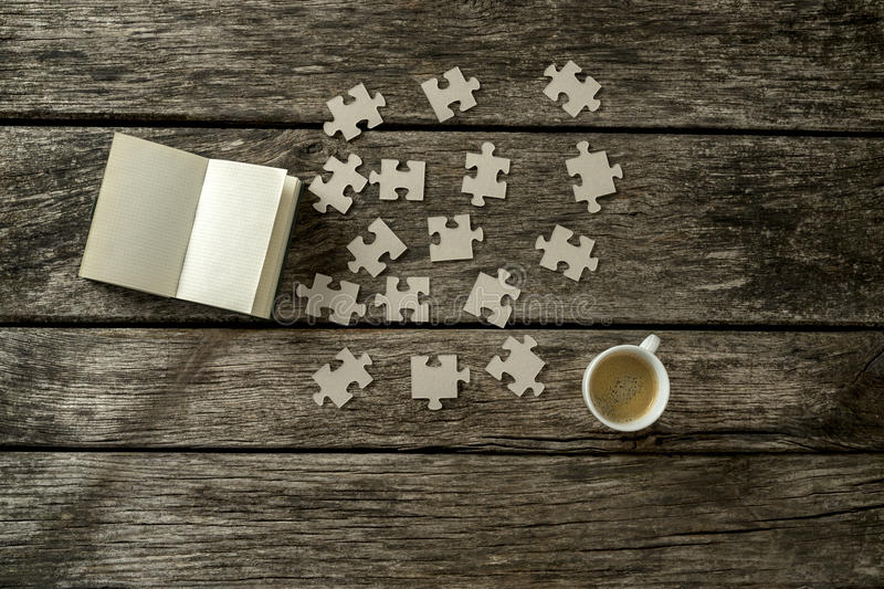 Top view of puzzle pieces scattered on a rustic wooden study desk with cup of coffee and open notepad alongside royalty free stock photos