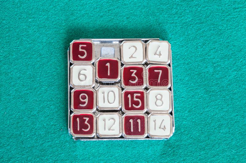 Top view of 15-puzzle sliding puzzle game. Top view of 15-puzzle magic 15 sliding puzzle game on green baize table stock photography
