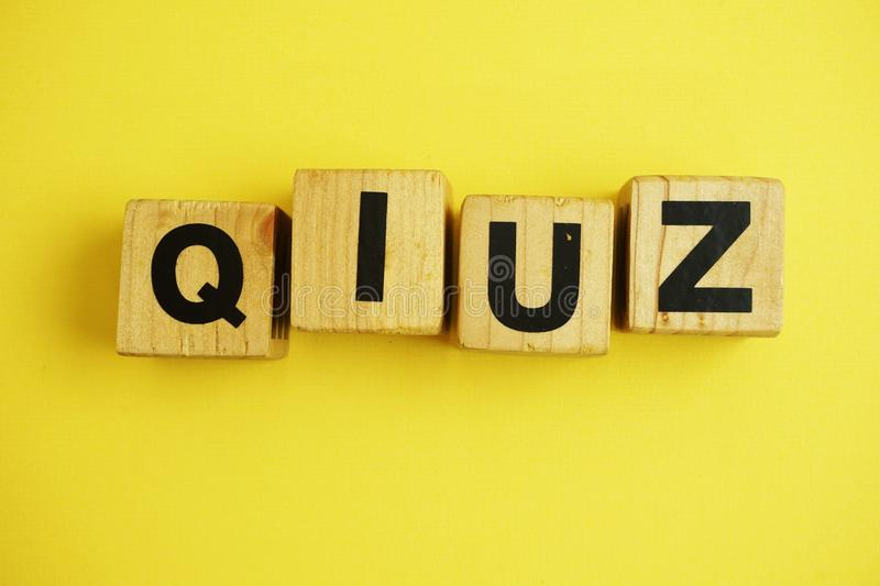 Quiz letters alphabet wooden cubes on yellow background. Top view quiz letters alphabet wooden cubes on yellow background stock image