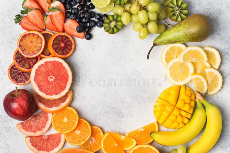 Top view of rainbow fruits and berries. Healthy eating, top view of healthy fruits in rainbow colours in a frame, strawberries, mango, grapes, bananas stock photos