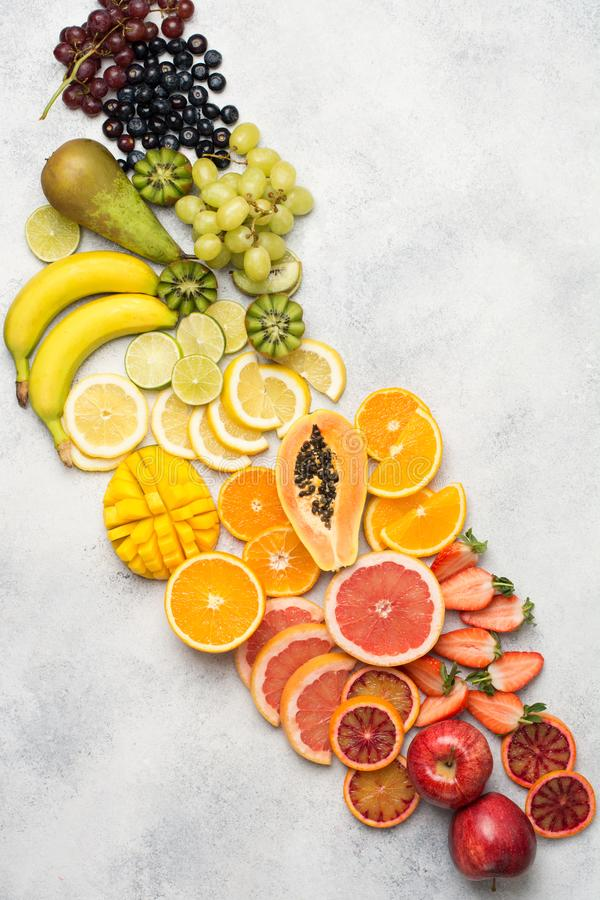 Top view of rainbow fruits and berries. Top view of colourful fruits in rainbow colours, strawberries, mango, grapes, bananas, oranges on the off white table royalty free stock images