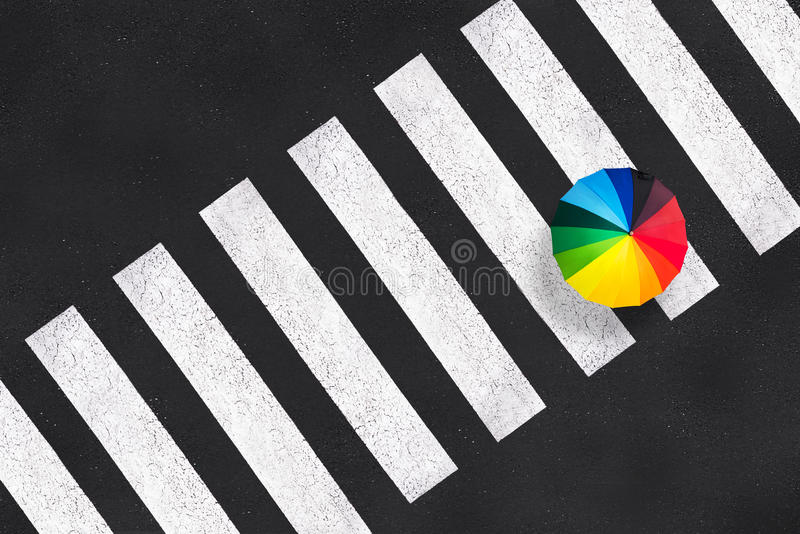 Top view of a rainbow umbrella on a pedestrian crosswalk. Aerial view of a rainbow umbrella on a pedestrian crosswalk stock image