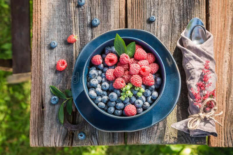 Top view of raspberries and blueberries in blue bowl. On old wooden table stock images