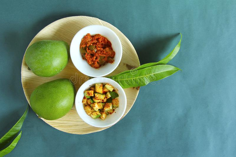 Top view, raw mango, its pieces and mango pickle isolated on green background stock photo