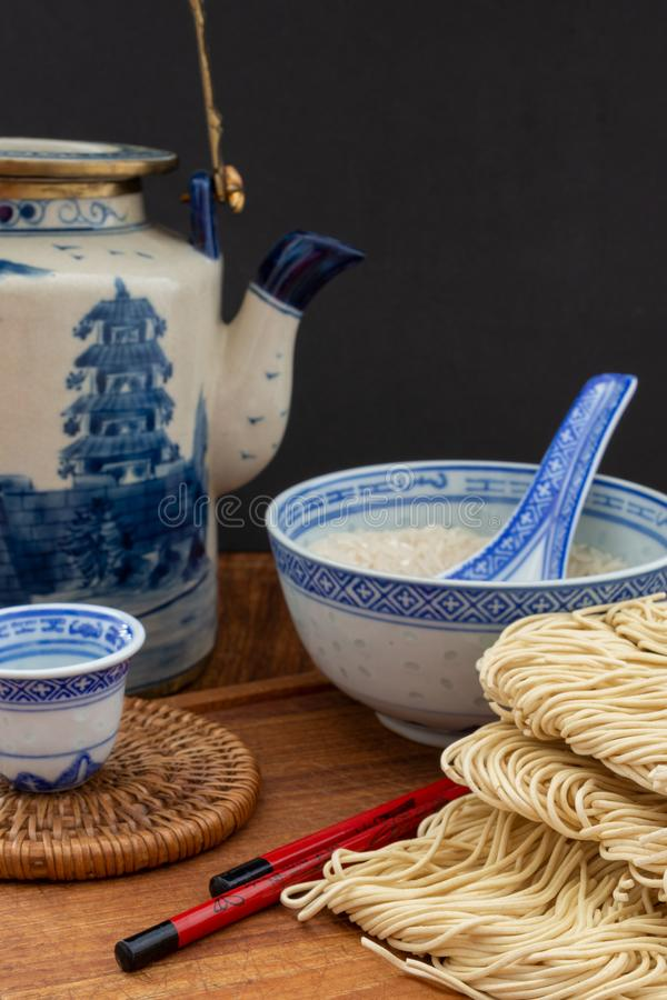Top view of raw noodles with rice bowl, teapot, chopsticks on wooden board stock images