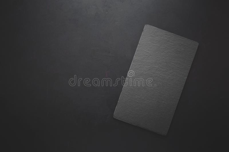 Top view on rectangle black slate plate on rustic dark background. Copy space. Toned royalty free stock photo