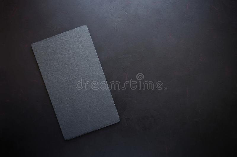 Top view on rectangle black slate plate on rustic dark background. Copy space. Toned.  royalty free stock photography