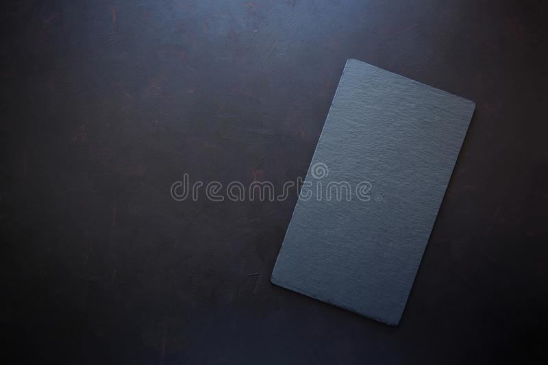 Top view on rectangle black slate plate on rustic dark background. Copy space.  royalty free stock image