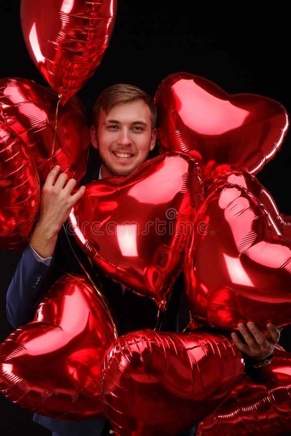 A top view on a red balloons in male hands on a black background. Valentine day concept. royalty free stock image