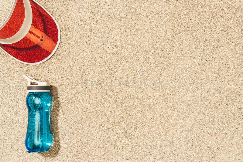 Top view of red cap and water bottle. On sand royalty free stock photos