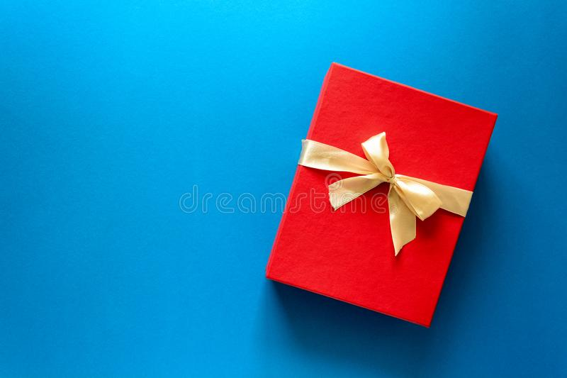 Top view on red Christmas gift box decorated with ribbon on blue paper background. New Year, holidays and celebration decorations concept. Copy space. Flat lay stock photo