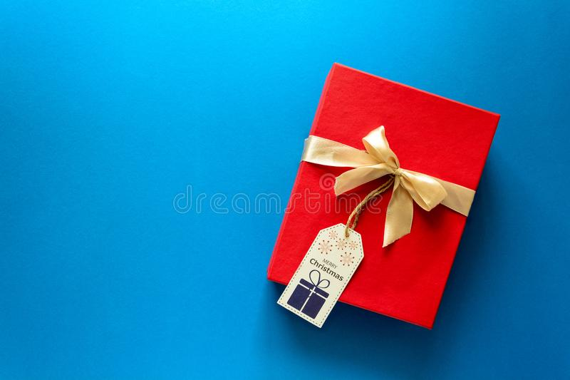 Top view on red Christmas gift box decorated with ribbon on blue paper background. New Year, holidays and celebration decorations. Concept. Copy space. Flat lay stock photos