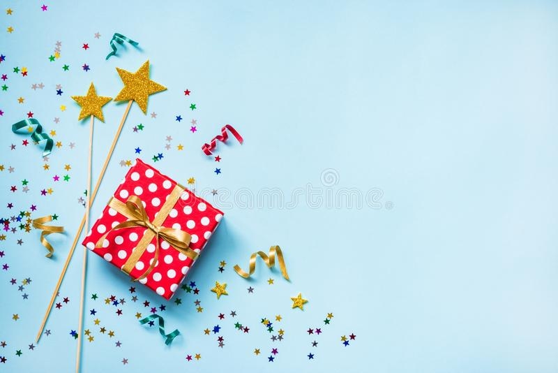Top view of a red dotted gift box, golden magic wands, colorful confetti and ribbons over blue background. Celebration concept. Co. Py space royalty free stock photo
