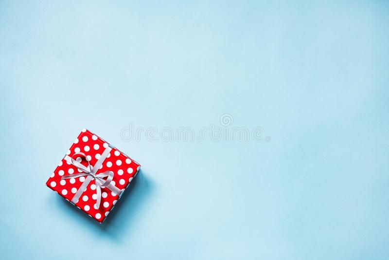 Top view of a red dotted gift box tied with silver bow over blue background. Copy space. stock images
