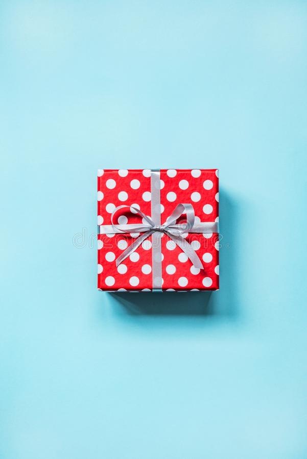 Top view of a red dotted gift box tied with silver bow over blue background. royalty free stock image