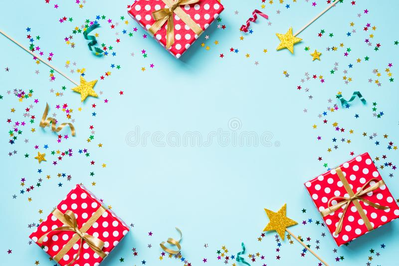 Top view of a red dotted gift boxes, golden magic wands, colorful confetti and ribbons over blue background. Celebration concept. Copy space royalty free stock photo