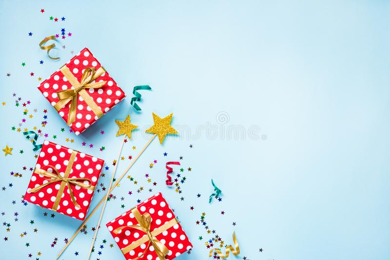 Top view of a red dotted gift boxes, golden magic wands, colorful confetti and ribbons over blue background. Celebration concept. stock photo