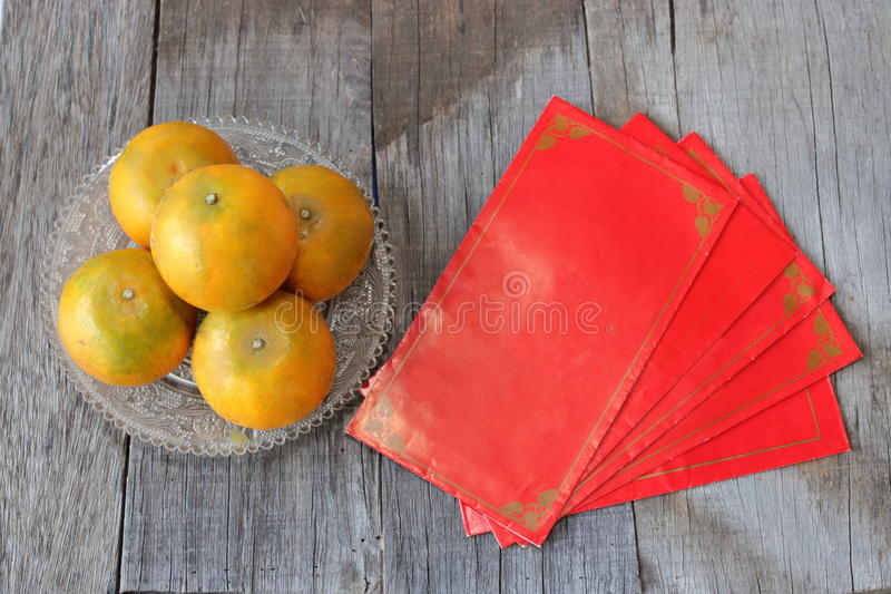 Top view of red envelope packet or ang paw and oranges in a bowl on old wooden background. Chinese new year festival concept royalty free stock image
