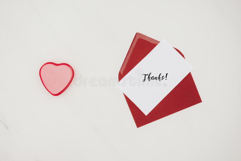 Top view of red envelope with THANKS lettering on paper and heart shaped box. Isolated on white royalty free stock images