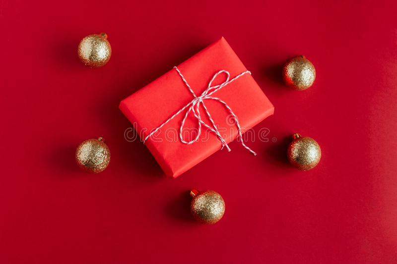 Red gift box and golden christmas balls on a red background stock image