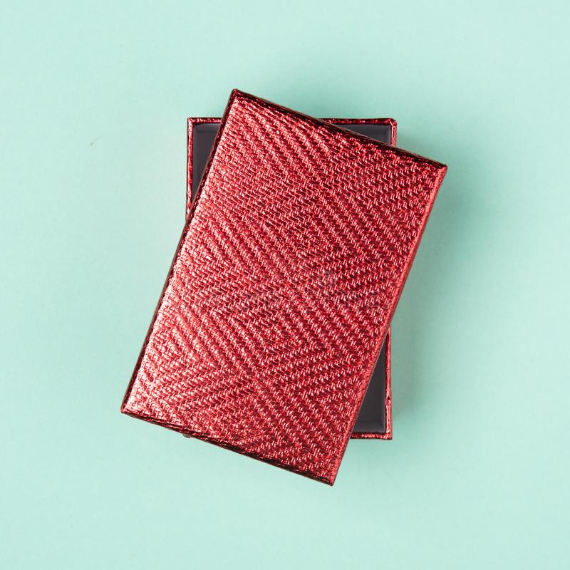 Top view on red gift box on neon mint background with copy space for design templates. Present concept. stock photo