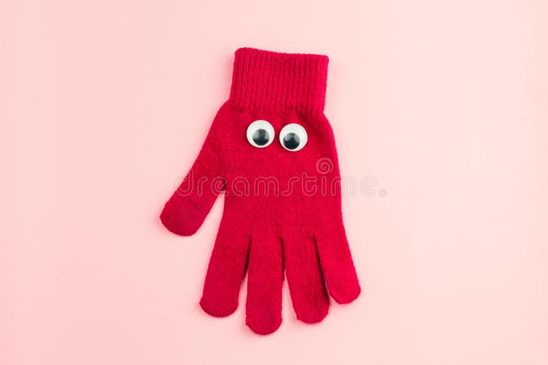 Red glove with googly eyes isolated on a pink background. Top view red  glove  with googly eyes isolated  on a pink background royalty free stock image