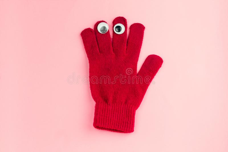 Red glove with googly eyes isolated on a pink background. Top view red  glove  with googly eyes isolated  on a pink background royalty free stock photography