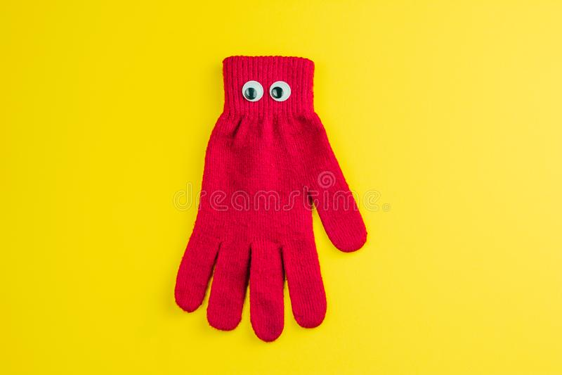 Red glove with googly eyes isolated on a yellow background. Top view red  glove  with googly eyes isolated  on a yellow background stock photography