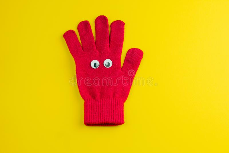 Red glove with googly eyes isolated on a yellow background. Top view red  glove  with googly eyes isolated  on a yellow background royalty free stock image