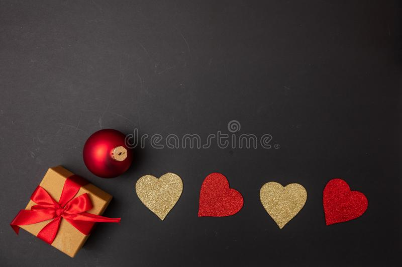Top view of red and golden hearts, a gift box with red ribbon and a christmas ball, black background royalty free stock image