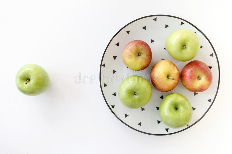 Top view of Red and green apples in white plate with black triangles pattern and green apple on white background stock photography
