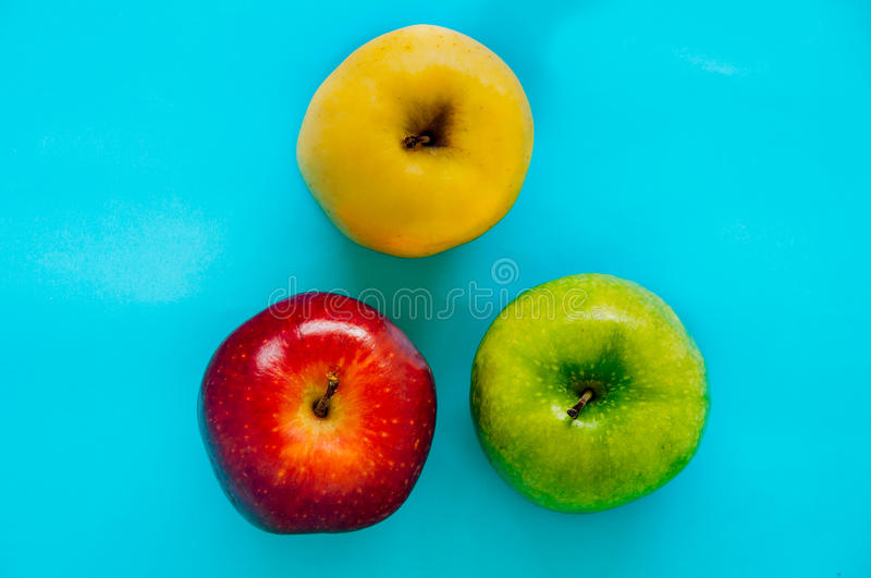 Top view of Red, green and yellow apple different in color on a. Top view of Red, green and yellow apple different in colors on a blue background ,Diversity royalty free stock images