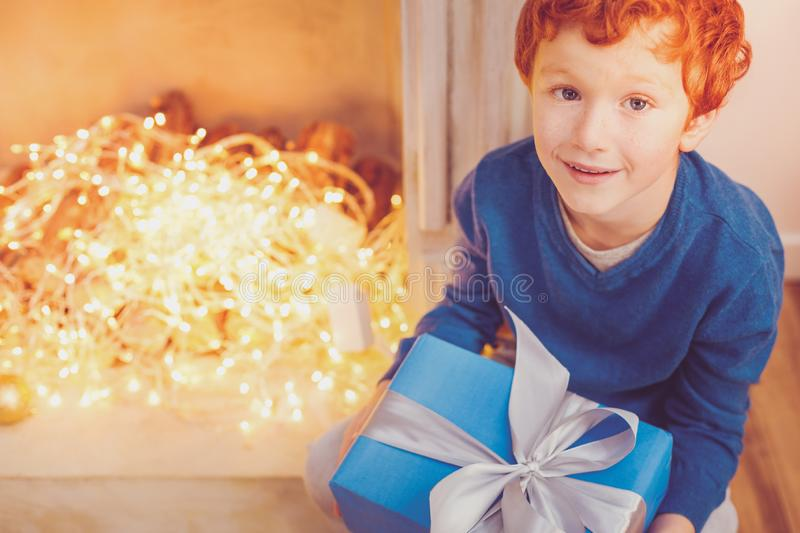 Top view of red-haired boy holding Christmas present stock image