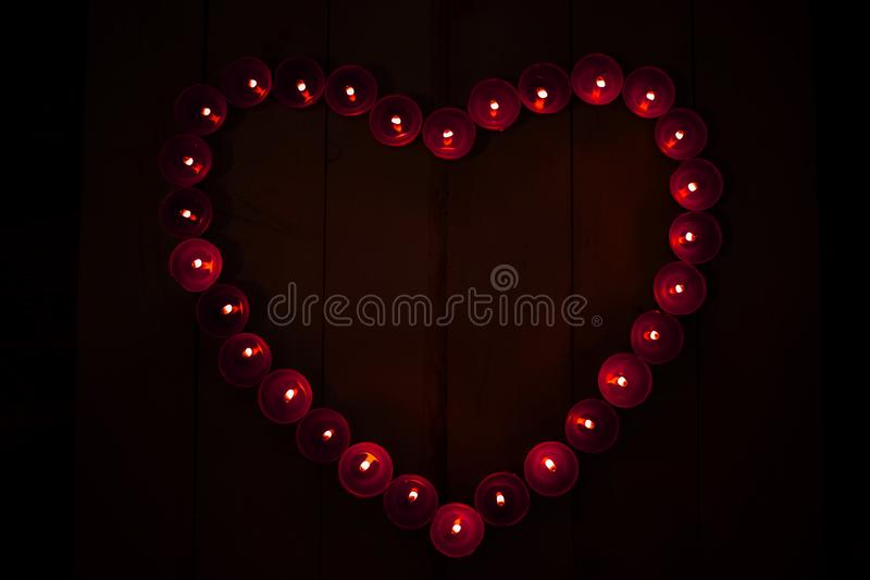 Top view of red heart of burning candles on black background in darkness. Valentine`s Day royalty free stock photography