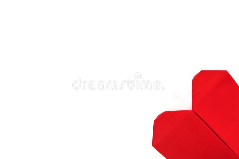 Top view of red heart paper origami on the right bottom corner of white background stock photo