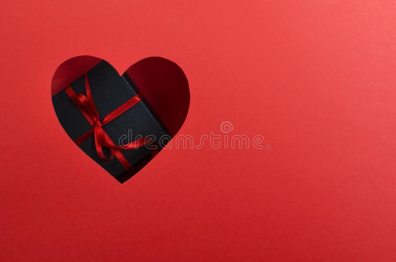 Top view of red heart shape and dark blue gift box with red ribbon and bow.Concept of romantic present for holiday.Empty space for royalty free stock photos